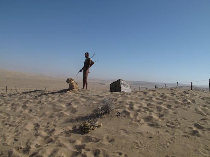 San bushman standing with a Cheetah