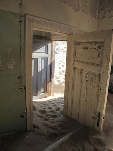 Door in abandoned house pushed open by sand