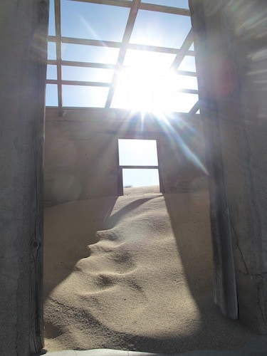 Sun shining through old roof of a house filled with sand