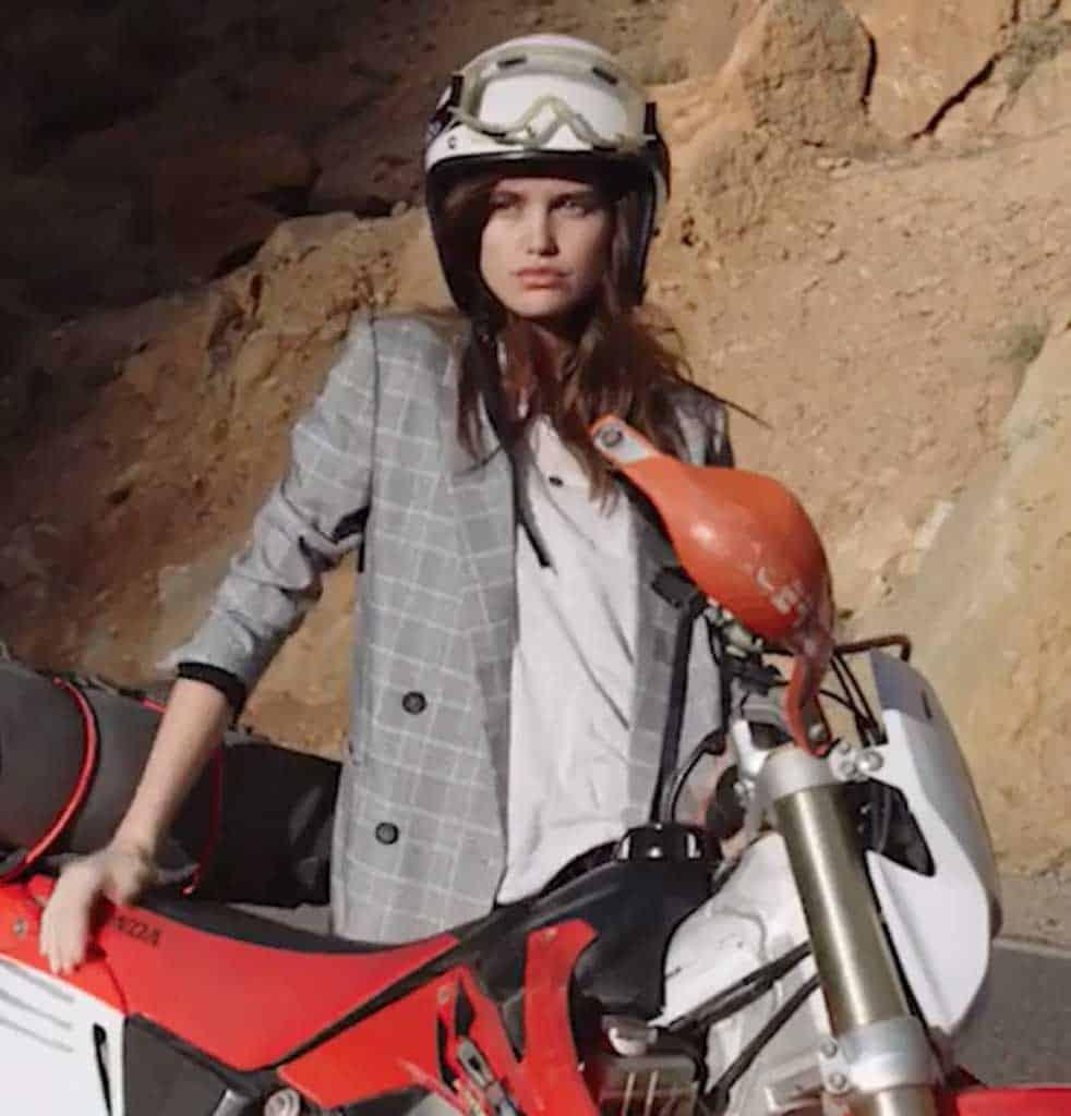 Girl standing by motox bike for film shoot