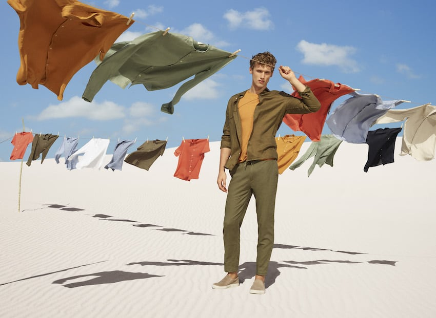 Male model in the desert with coloured hanging shirts
